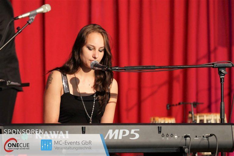 Sam spiel Keyboard und singt auf einer Bühne