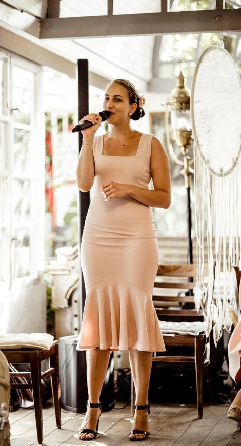 Wild Hearts, Sam, Traurednerin, Sängerin, auf einer Hochzeit in einem rosa Kleid. Im Hintergrund sind einige alte Holzstühle und ein weißes Fenster zu sehen, großer Traumfänger, Macramee, Rosa